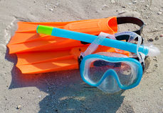 Diving mask, snorkel and fins on a sandy beach. Brightly colored diving mask, snorkel and fins on a sandy beach Royalty Free Stock Images