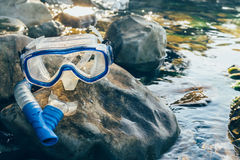 Diving Mask And Snorkel Lie on The Stones, On The Sandy, Closeup. Tourism Travel Freediving Concept. Equipment of freediver on pebble coast near the sea, mask Stock Photos