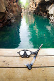 Diving mask and snorkel lying on wooden pier with Royalty Free Stock Images
