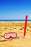 Diving mask and snorkel in the sand of a beach. A diving mask and a snorkel in the sand of a beach Stock Photos