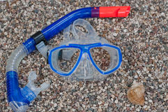 Diving mask with snorkel and shell on beach. Diving mask with snorkel and shell on background of stony beach Stock Images