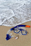 Diving mask and snorkel on the shore. Diving mask, snorkel and seashell laying on sand and washed by surf Royalty Free Stock Photography