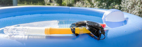 Diving mask and snorkel at the swimming pool. Diving mask and snorkel at the blue swimming pool Royalty Free Stock Photos