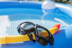 Diving mask and snorkel at the swimming pool. Diving mask and snorkel at the blue swimming pool Royalty Free Stock Photo