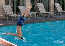 Diving into the pool. Young boy diving head first into a swimming pool with head in the water and feet still in the air Royalty Free Stock Photos
