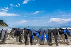Diving suits drying on a wall Stock Photos