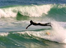 Diving Surfer. Surfer diving into the Mediterranean sea to catch a wave Stock Photography