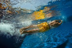 Diving into swimming pool. Portrait of a male swimmer, that jumping and diving into swimming pool.Low angle view from the swimming pool Stock Images