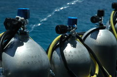 Diving tanks. Grey diving tanks on a boat, water in background Stock Images