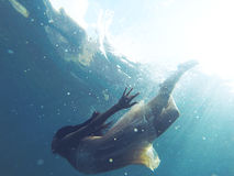 Diving. Underwater photo of a human diving in blue sea water royalty free stock photography