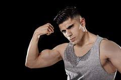 Diviértase al hombre con el cuerpo atlético grande y fuerte que presenta con el brazo doblado mostrando el pecho y hombros del mú Imágenes de archivo libres de regalías