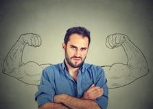 Diviértase al hombre joven con enorme, falso, los brazos del músculo dibujados en la pizarra Imágenes de archivo libres de regalías