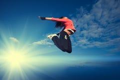 Diviértase a la mujer que salta y vuele sobre el cielo y el sol Imágenes de archivo libres de regalías