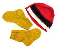 Divirtiéndose un casquillo y un amarillo rojos hizo punto los calcetines de lana aislados en el fondo blanco Imagenes de archivo