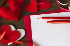 Divisez en lots les coeurs du feutre, de bande paerforée, du crayon et du stylo Photographie stock libre de droits