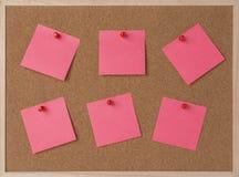 Divisez en lots une note collante rose sur le panneau de liège de cadre en bois Images stock