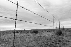 Division. S.  Looks the same to me.  Pick your side. Barbed wire fence line in a very empty corner of eastern Oregon on a stormy day.  Black and white with focus Royalty Free Stock Image