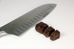 Division equally candy. Cutting candy four share knife on a cutting Board Stock Photo