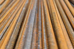 Division rebar - a closeup of rusty vertically stacked iron or steel reinforcement bars. Vertically aligned ribbed steel rods, so called rebar, commonly used in Royalty Free Stock Photography