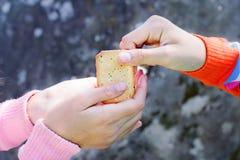 Divisione dell'alimento Donne che danno un cracker ad un piccolo bambino Carità c fotografie stock libere da diritti