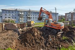 Excavator woking on constraction site. Divnogorsk, Russia - June 16: Construction of a house, preparation of a trench with the technics in Divnogorsk, Russia on Royalty Free Stock Photography