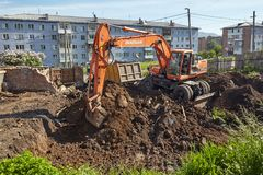 Excavator woking on constraction site. Divnogorsk, Russia - June 16: Construction of a house, preparation of a trench with the technics in Divnogorsk, Russia on Royalty Free Stock Photos
