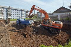Excavator woking on constraction site. Divnogorsk, Russia - June 16: Construction of a house, preparation of a trench with the technics in Divnogorsk, Russia on Stock Photo