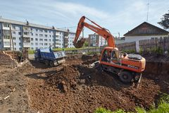 Excavator woking on constraction site. Divnogorsk, Russia - June 16: Construction of a house, preparation of a trench with the technics in Divnogorsk, Russia on Stock Image