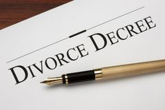 Divorce. Decree and gold fountain pen shot on warm wood surface