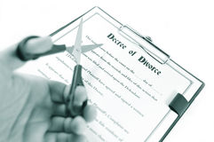 Divorce. Decree and hand holding scissors isolated against white Stock Photo