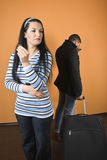 Divorce. Couple divorce,woman standing with wedding ring in hand and cry away and man leave the house with baggage,check also Couples Stock Image