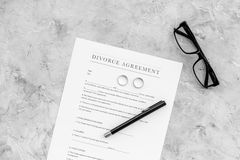 Divorce agreement. Wedding ring on document on grey background top view copy space Stock Image