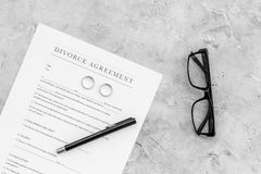 Divorce agreement. Wedding ring on document on grey background top view copy space Stock Photo