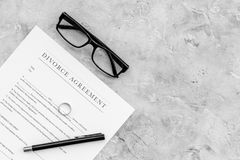 Divorce agreement. Wedding ring on document on grey background top view copy space Stock Photos