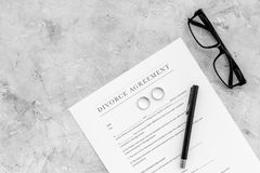 Divorce agreement. Wedding ring on document on grey background top view copy space Stock Photography