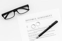 Divorce agreement. Wedding ring on document on white background top view copy space royalty free stock images