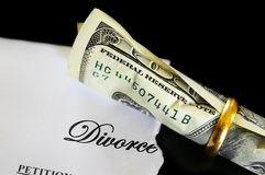 Divorce cash. Divorce decree and rolled up cash in a wedding ring Stock Photo
