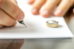 Divorce. Closeup of male hand signing divorce papers stock image