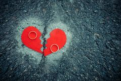 Divorce concept - broken heart with wedding rings on cracked asphalt. Toned stock photo