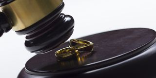 Divorce concept. Close up of wedding rings and judge gavel royalty free stock image