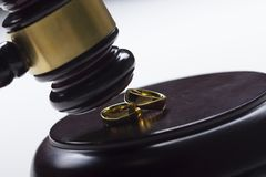 Divorce concept. Close up of wedding rings and judge gavel stock photography