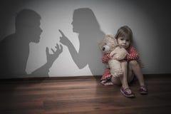 Divorce concept. Sad child is sitting at floor when parents argue.