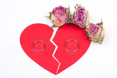 Divorce concept - wedding rings on red broken heart with dry flo Royalty Free Stock Photos