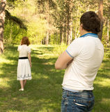 Divorce, couple problems. Divorce conflict separation concept, couple problems, unhappy women (wife) going away from men (husband) outdoor in summer park Royalty Free Stock Image