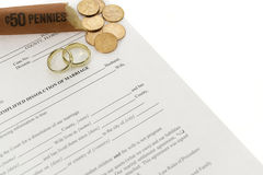 Divorce Form With Open Roll Of Pennies. Also two wedding rings laying on form. Done on white background Royalty Free Stock Photos