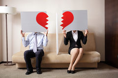 Divorce. Sad young couple holding billboard sign with break love heart, concept for