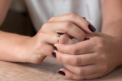 Divorce, separation: woman removing wedding or engagement ring. Divorce, separation: hands of woman removing wedding or engagement ring Royalty Free Stock Images