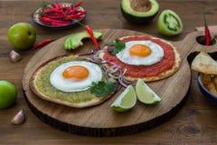 Divorciados Huevos, очень вкусная еда с яичками, свежий салат и соус трав пряный herby стоковое фото