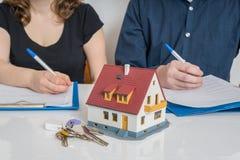 Divorcie-se e dividindo um conceito da propriedade O homem e a mulher estão assinando o acordo do divórcio fotos de stock
