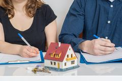 Divorcie-se e dividindo um conceito da propriedade O homem e a mulher estão assinando o acordo do divórcio foto de stock royalty free